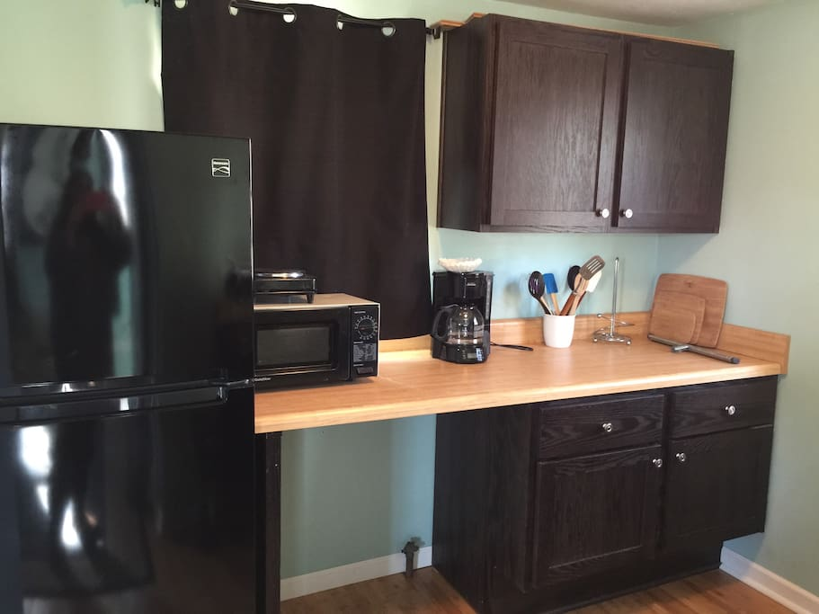 Part of kitchen area which includes refrigerator, counter space, microwave, coffee maker, hotplate.