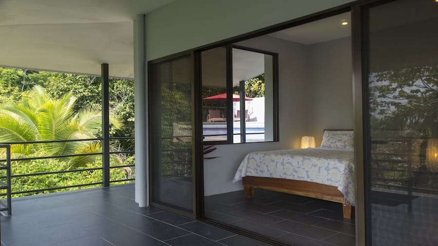 Queen bedroom opens up to the large balcony with mountain views.