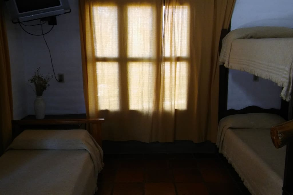 la cama simple y cucheta en el estar