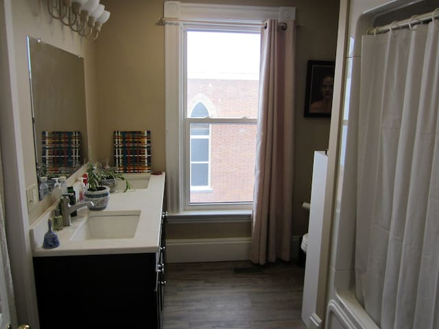 double sink bathroom with large tub and shower