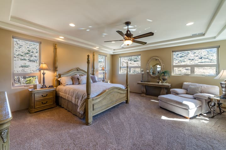 Master Bedroom with King bed, balcony off master with salt hotub and mountain views, electric blinds, smart tv with xfinity cable and dvd player.
