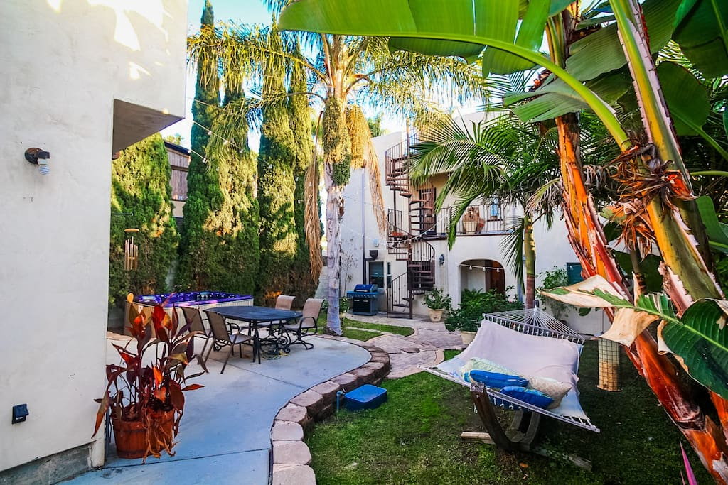 Huge lush backyard with plenty of space and relaxing atmosphere including fire pit, multiple lounges, dining table and a spa