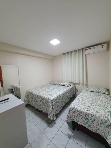 Quarto 2, com uma cama queen e uma cama solteiro, Tv, ar condicionado, cômoda, espelho e cortina Black-out.