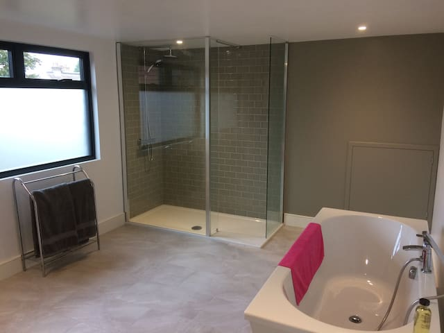 Separate loft bathroom with free standing bath and double shower.