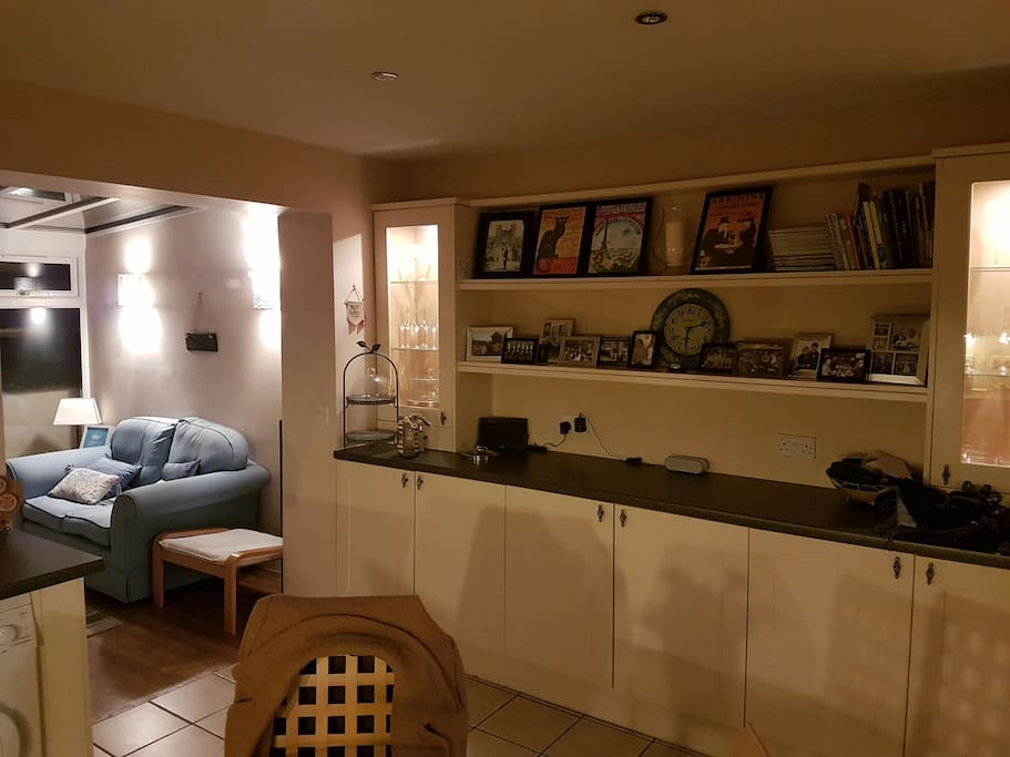 Kitchen with table and chairs for four people, and access to small conservatory seating four people