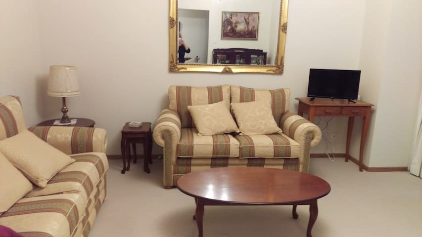 Separate lounge with small dining table/chairs, fridge, tv with DVD player, some DVDs.  Overlooks front garden.