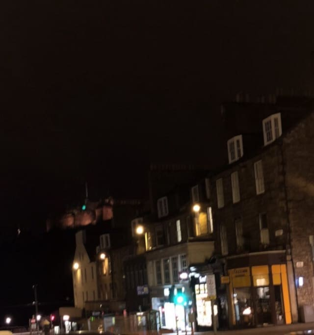 The flat is above the yellow shop Edinburgh Castle is behind it