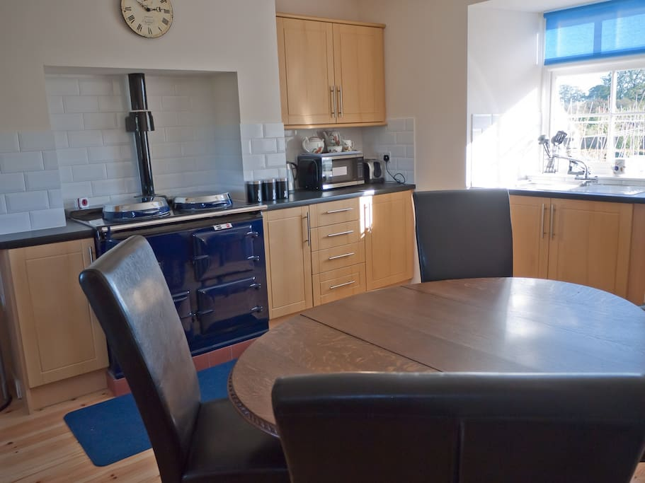 Dining kitchen with Aga, microwave, and dining table to easily seat 6 persons.