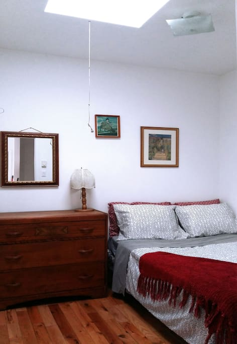 Room with a sunlight and a comfy bed which sleeps two. Dresser and hanging rack for your clothing.