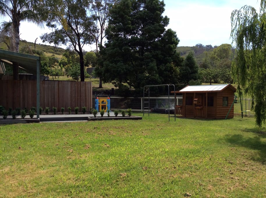Large fenced backyard with children's cubby and sandpit