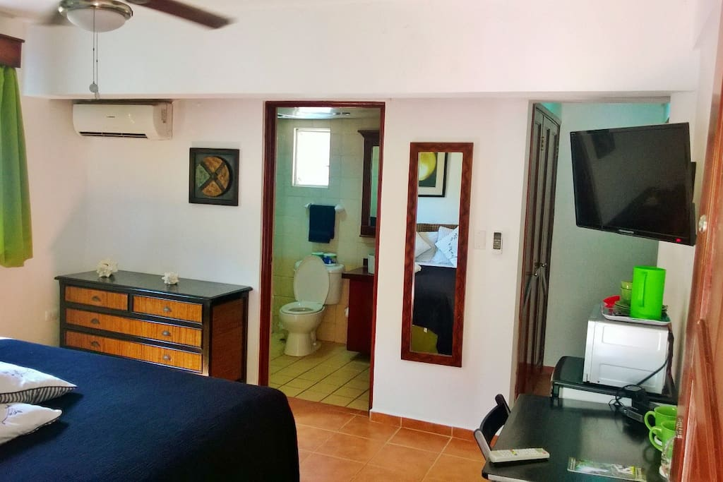 Spacious bedroom with A/C, 32 inch TV, fridge, small table, coffee machine, microwave and  closet in the back