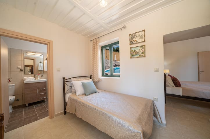 The third bedroom with a single bed and an antique wooden closet and the second bathroom. The twin bedroom and the single bedroom are connected and are not separate by a door.