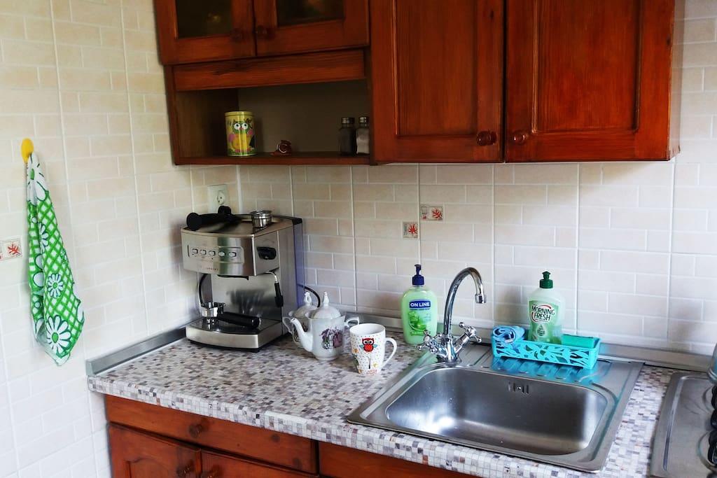 Кухня. Газовая плита, микроволновая печь, холодильник, кофемашина, кухонная утварь, посуда.
