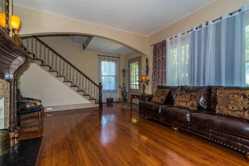 Standing in the formal living room, the honey glow of the original heart pine floor points you to the beauty of the intricately designed 19th century chocolate fireplace mantle. To your right is the original staircase.