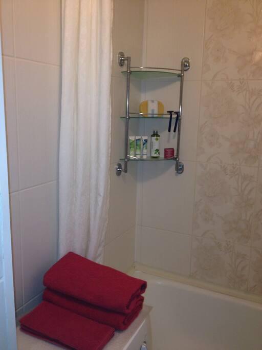 Ванная комната со стиральной машиной, свежими полотенцами и предметами личной гигиены