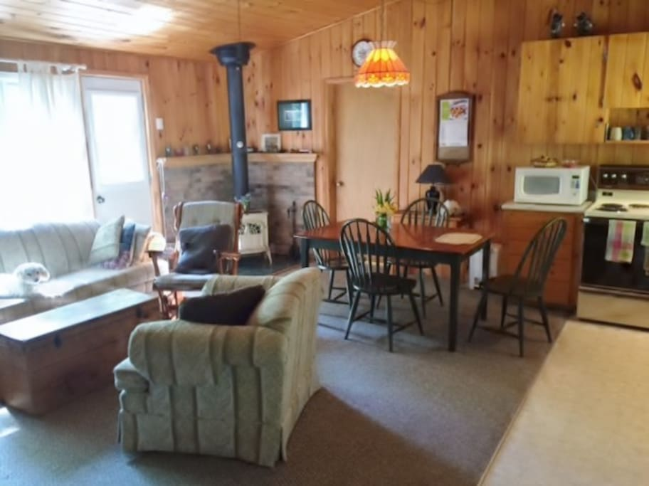 Sunny interior showing large picture window, living/dining area and and wood stove.