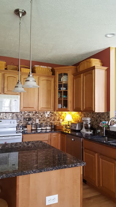 Luxury kitchen with island seating for four includes full set of dishes and cookware.