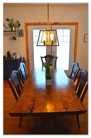 Dining room with large custom built live-edge table and doors opening on to large deck and outdoor dining & BBQ space