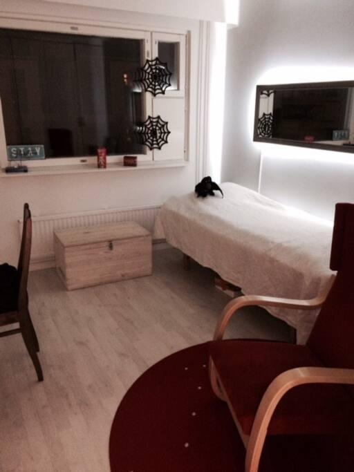 Huone, jossa sänky, nojatuoli ja pöytätaso.