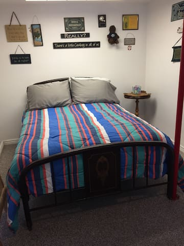 Old fashioned double size bed with a feather tic mattress.