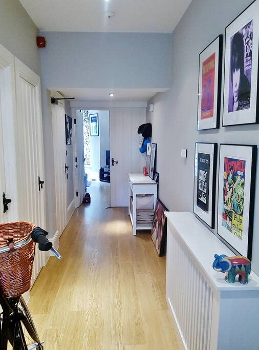 Long, stylish hallway with local artwork.