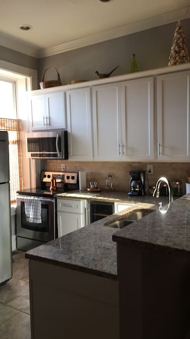 Kitchen features granite counter tops, all new dishes, glasses ( wine glasses too!), cookware, toaster, coffee maker, wine cooler, counter stools, and stainless steel appliances. Complimentary coffee and tea with creamer.