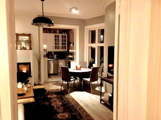 Stue/Spisestue med åpning mot kjøkkenet. Stor sofa, TV, Peis og Spisebord som kan trekkes ut så det kan sitte 8-10 rundt. Her er bordet på det miste med 4 stoler rundt