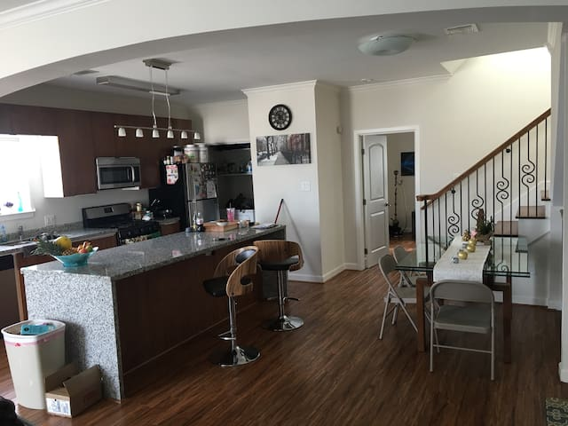 Gas stove, washer and dryer, dishwasher, microwave, kitchen table, and bar stools.
