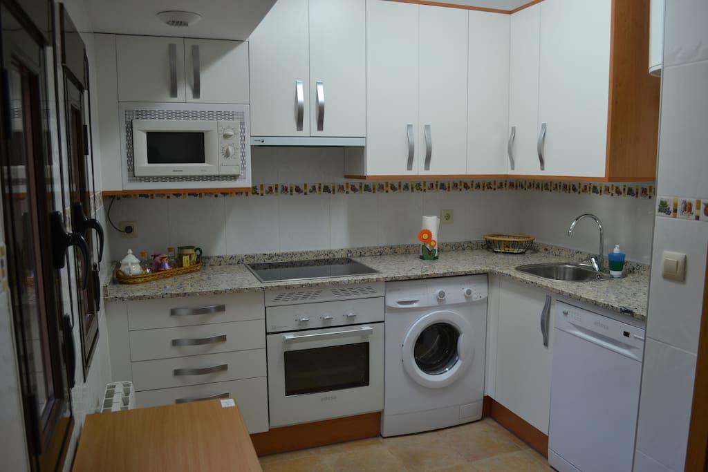 Cocina. Con lavadora, horno, frigorífico, vitrocerámica y microondas.