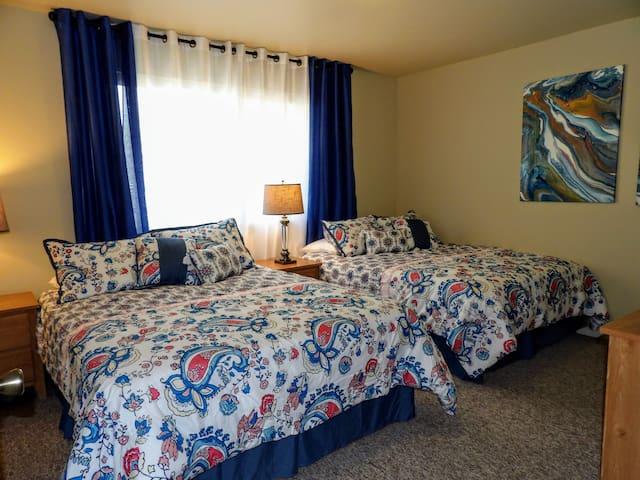 Bedroom 1 has 2 Queen Beds with separate Nightstands and Lamps