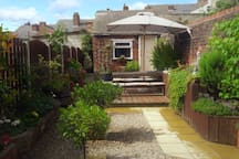 Relax in our south facing sunny garden, with table, seating & outdoor lighting plus secure outhouse storage shed for cycles