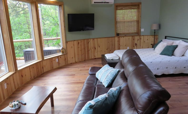 Open living room and bedroom with views out 5 large plate glass windows.