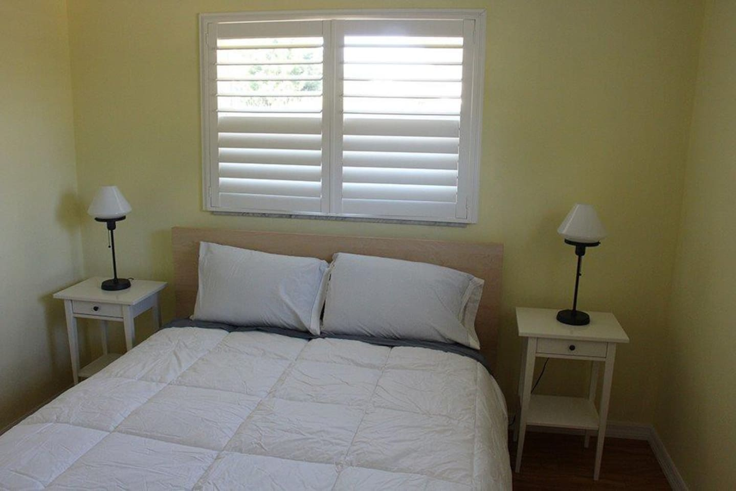 Queen bed. Window treatments that enable occupant to control the light in the room.