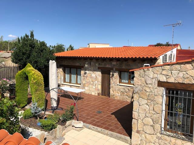 Fachada del Salón/ Comedor de piedra, el patio y parte del jardín.