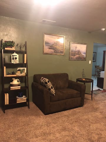 Single sofa sleeper in living room, linens are in the hall cabinet.