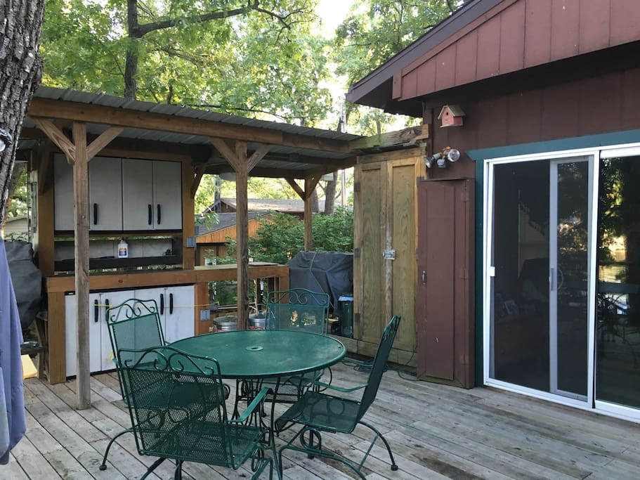 Outdoor kitchen with refrigerator makes this a great place to eat in warm weather.