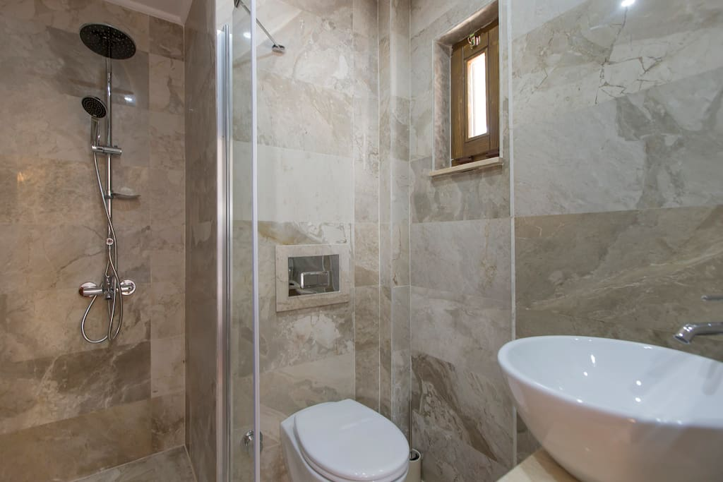 Modern bathroom with powerful shower and locally made olive oil toiletries