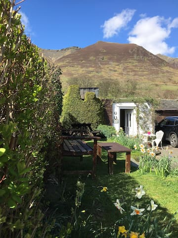 The annex room door way with Blencathra in the background outside seating for guests use