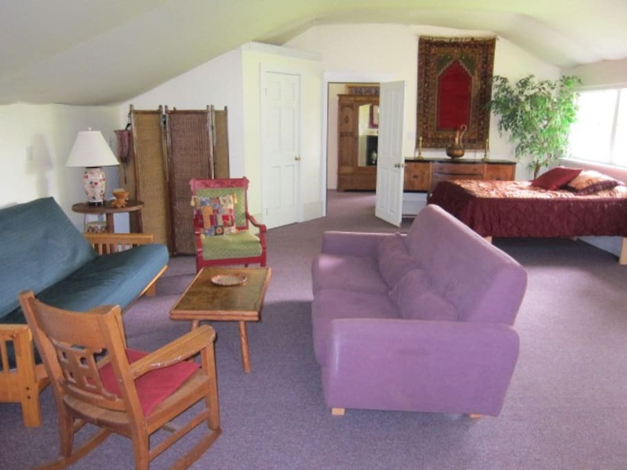 First sitting room has a bay window, two couches, one is a queen futon that folds out to an extra bed, and a double bed. Unique ceiling made of muslin fabric.