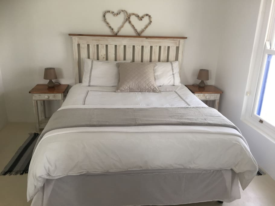 Comfortable queen size bed with crisp white linen