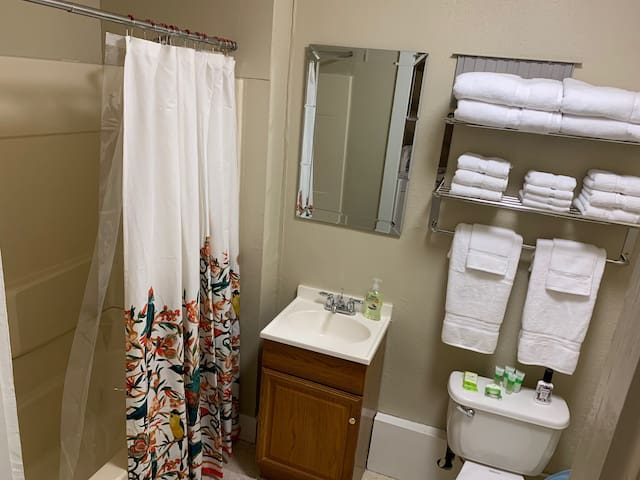 Full bathroom in The Caroline with tub/shower, towels and wash cloths, toiletries