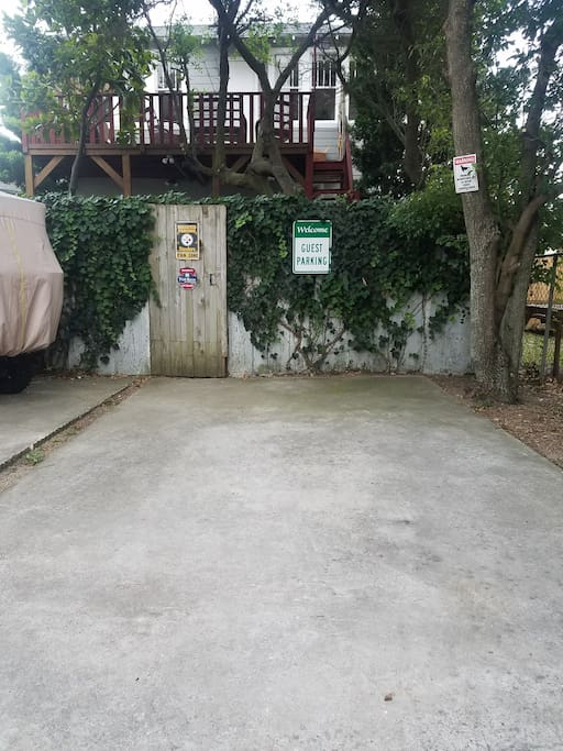 Guest parking at rear of home, access by paved alley with private keypad entry, security camera.  Self check in.
