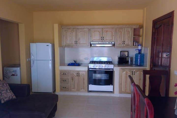 Cocina con horno, nevera, micro ondas, lavadora, tostadora y enseres necesarios para cocinar y comer.