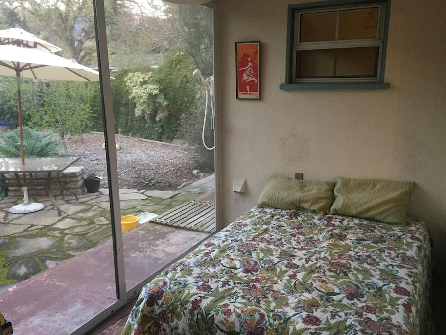 The guest room: a double bed with screen doors to the backyard