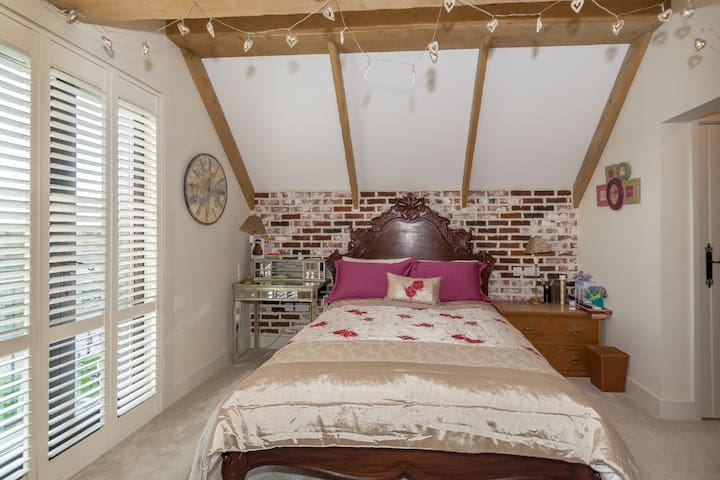 Double bed with feature bathroom with bath and walk in shower