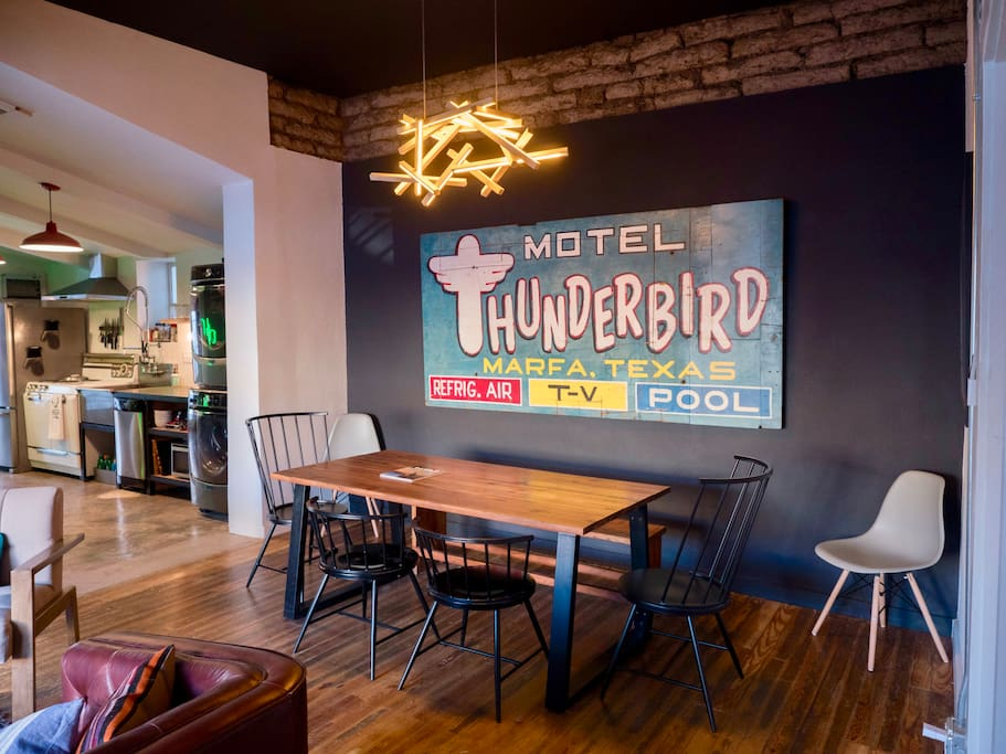 A recovered billboard for the Thunderbird Motel serves as the centerpiece for the dining area.