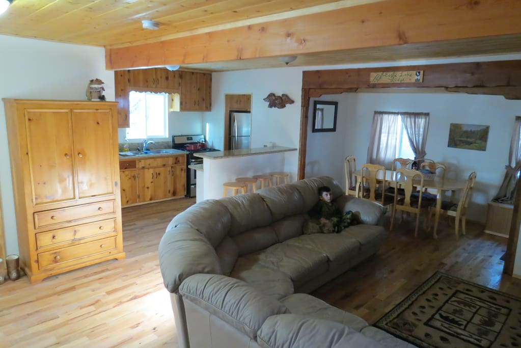 Open living room, dining area, and kitchen. Rustic cabin themed furnishings.