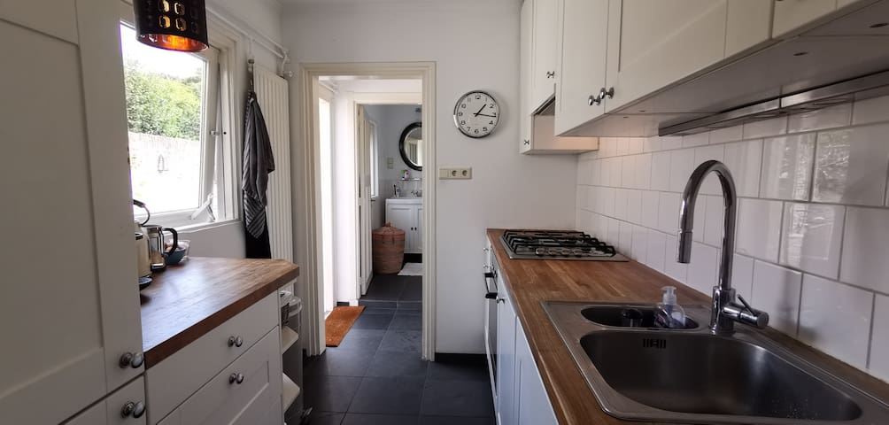 A look into the kitchen, with dishwasher, and bathroom at the end