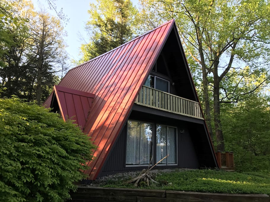 Classic A-Frame cottage with all it's charm and unique features. Restored red metal roof on wooded lot.
