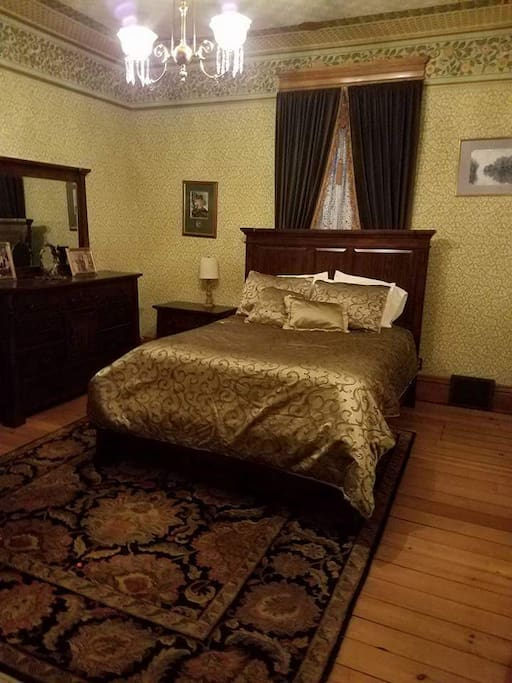 Guestroom 1 is the Gold bedroom of Waldheim, The John Lersch House. Room features dark cherry queen  bedroom set, hand carved mantled fireplace, and walk in closet. Several 1800 period antiques, Persian rug, and lights add to the beautifully decorated art nouveau decor.